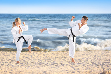 Young man and woman practicing karate outdoors 免版税图像