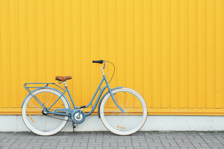 Retro bicycle near yellow wall outdoors Archivio Fotografico