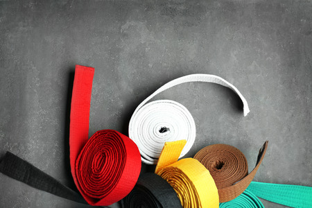 Colorful karate belts on grey background