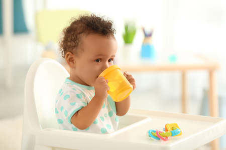 Cute baby drinking water indoors
