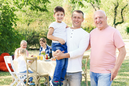 Happy family having barbecue party outdoors