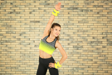 Sporty young woman training against brick wall
