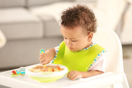 Petit bébé mangeant de la purée de fruits à l'intérieur