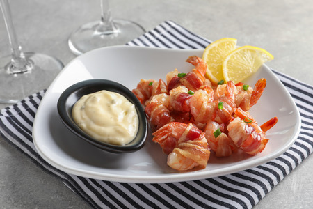 Plate with bacon-wrapped shrimps and tasty sauce on table