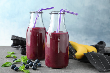 Glass bottles with acai juice on table Stock Photo