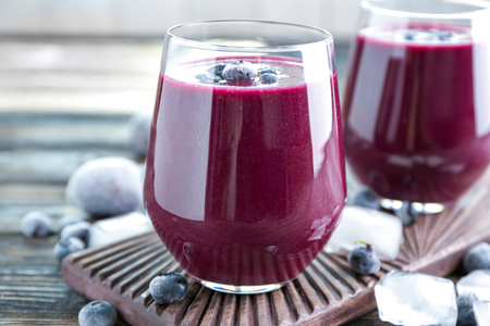 Glass with acai juice on wooden board
