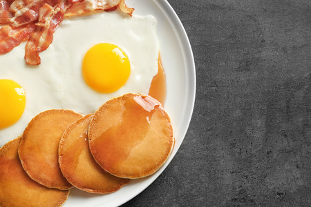 Tasty breakfast with pancakes, fried eggs and bacon on table Banque d'images