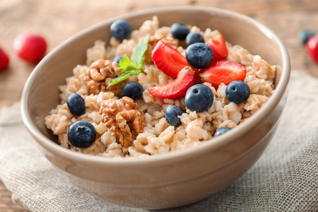 Tasty oatmeal with berries in bowl on table