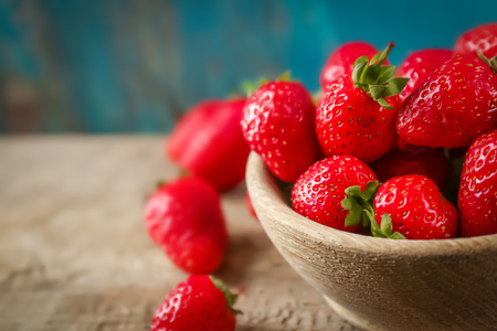 Bowl with fresh strawberries on wooden table, closeup