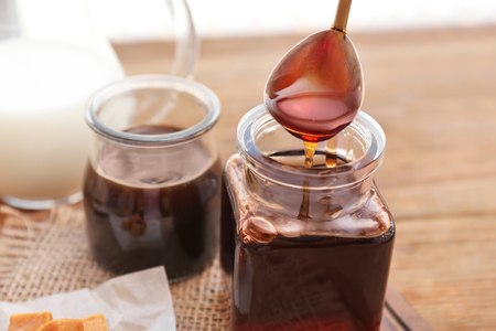 Spoon with tasty caramel sauce over jar, closeup