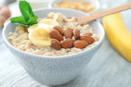 Tasty oatmeal with almonds and banana in bowl on table, close up Stock Photo