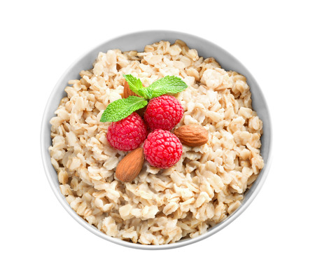 Tasty oatmeal with berries in bowl on white background 免版税图像