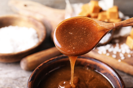 Łyżka ze smacznym sosem karmelowym nad miską, zbliżenie