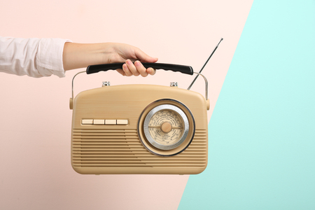 Woman holding radio on color background