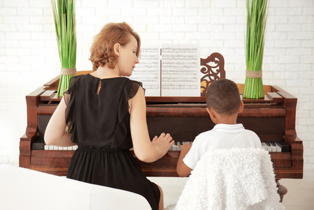 African-American boy with teacher learning to play piano indoors Stockfoto