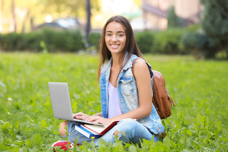 Pretty student with laptop studying outdoors