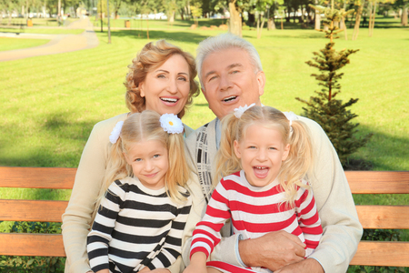 Elderly couple with granddaughters in park