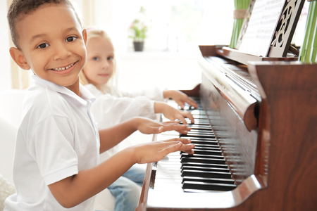 African-American boy with little girl playing piano indoors Imagens