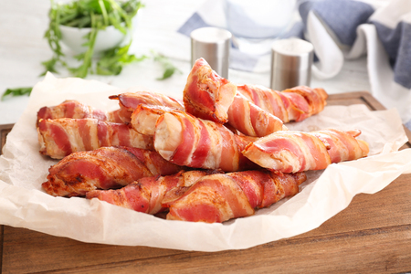 Bacon wrapped chicken nuggets on wooden board