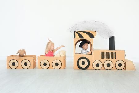 Niños jugando con tren de cartón en la sala de luz