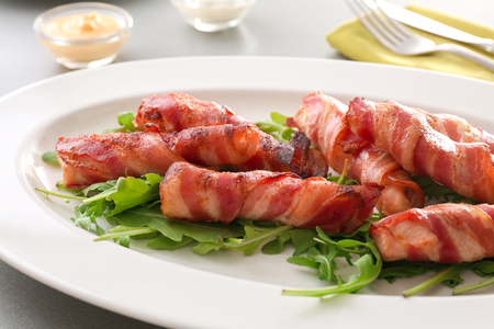 Plate with bacon wrapped chicken nuggets on table, closeup