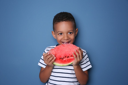 Cute African American boy eating watermelon on color background Stock Photo