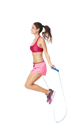 Young woman with jumping rope on white background