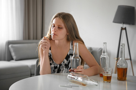 Young woman drinking alcohol and smoking cigarette at home 스톡 콘텐츠