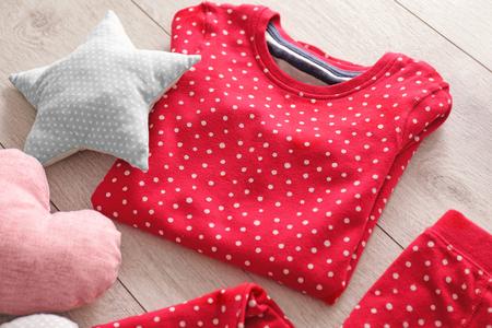 Composition with fashionable childish pajama on floor