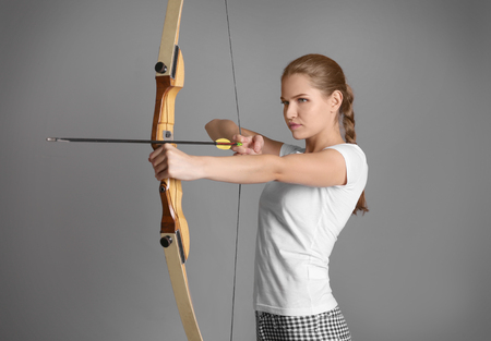 Young woman practicing archery on grey background Archivio Fotografico