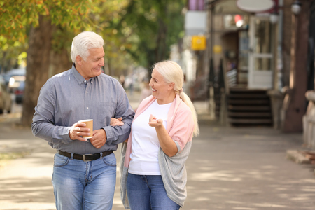 Mature couple with cups of coffee walking together outdoors