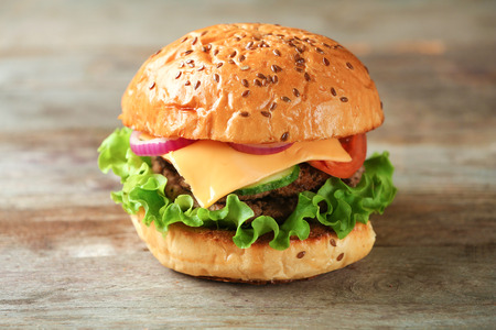 Tasty burger on wooden background