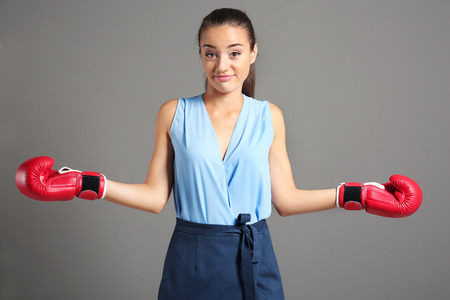 Businesswoman in boxing gloves on grey background 版權商用圖片