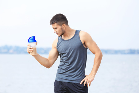 Handsome young man with protein shake on river bank Imagens