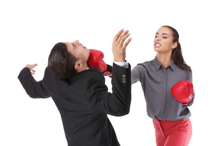 Woman in formal clothes and boxing gloves hitting businessman on white background Фото со стока