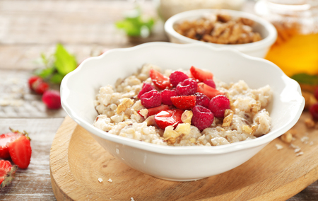 Delicious oatmeal porridge with strawberries and raspberries in bowl on table Banque d'images