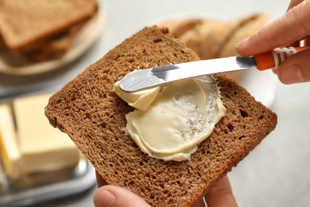 Woman spreading butter on slice of bread, closeup Reklamní fotografie
