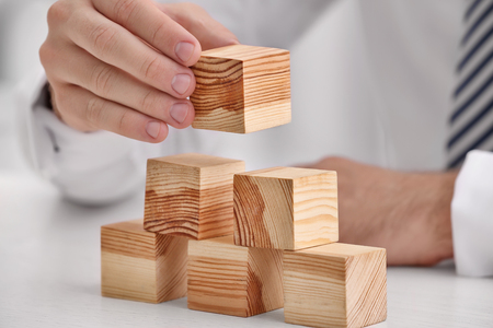 Young man with wooden cubes at table Stok Fotoğraf