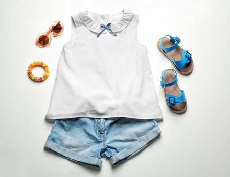 Child's clothes and sandals on white background