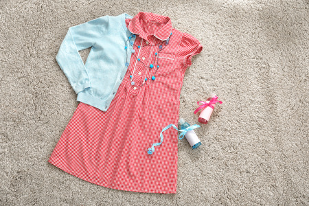 Stylish baby dress and accessories on fabric