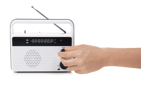 Hand of young woman with retro radio receiver on white background Imagens
