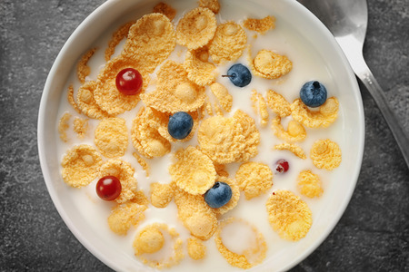 Dish with cornflakes and milk on table