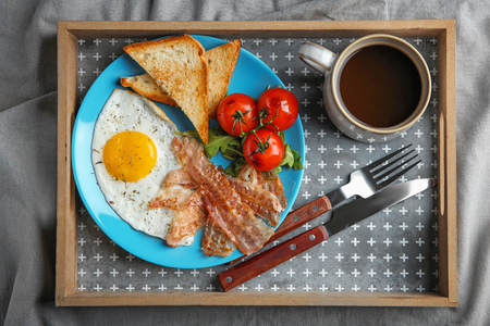 Plate with fried egg, bacon and tomatoes on tray Stock Photo
