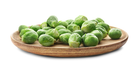 Wooden plate with Brussels sprouts on white background