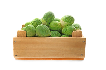Fresh Brussels sprouts in wooden box on white background