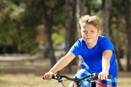 Niño con sobrepeso montando bicicleta en el parque Foto de archivo