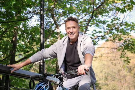 Mature sporty man with bicycle outdoors