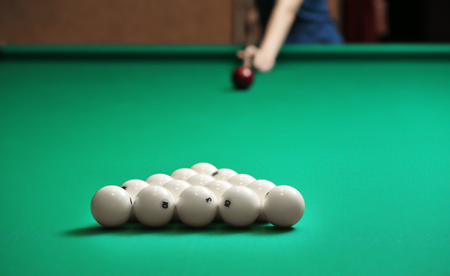 Pyramid of billiard balls on table with blurred woman on background
