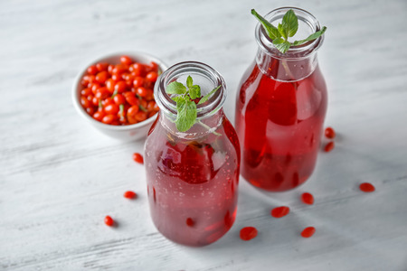 Bottles with healthy goji juice on wooden table