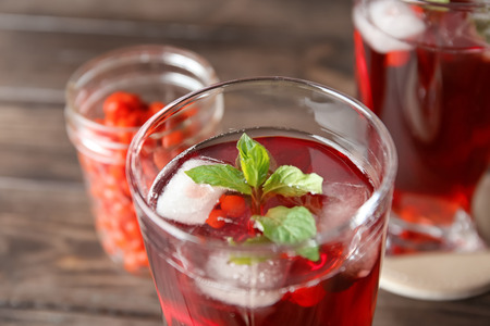 Glass with healthy goji juice on wooden table